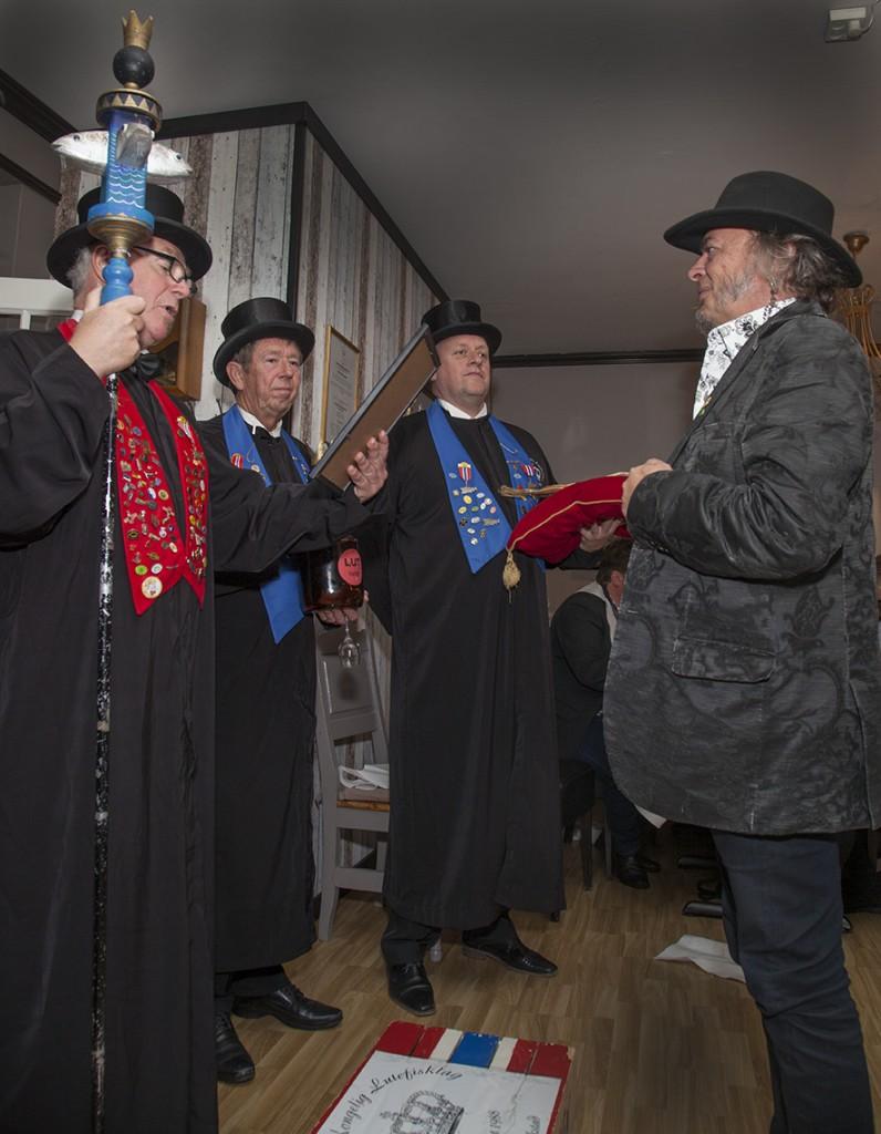Etter å han knelt på fiskekassen, smakt på luten og på tørrfisken, ble han av president Frank Jensen utnevnt til Gamlebyens Storelsker. De to andre på bildet er ambassadørene Bjarne Bjørkelo og Rune Solberg.